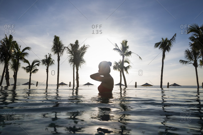 Danang, Vietnam - July 8, 2014: Young Asian woman swims in a pool at a beachside resort