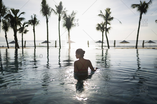 Danang, Vietnam - July 8, 2014: Young Asian woman in a pool at a beachside resort