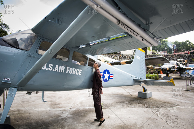 Ho Chi Minh City, Vietnam - May 26, 2014: A Vietnamese man peers inside of an old plane at the War Remnants museum
