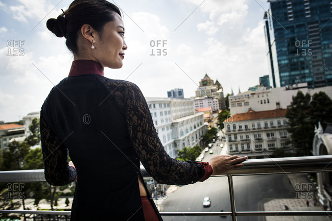 Ho Chi Minh City, Vietnam - May 27, 2014: A young woman looks over downtown from a small balcony at the Caravelle Hotel