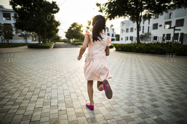 Young Vietnamese girl runs through a private drive as the sunsets in a suburban housing complex in Ho Chi Minh City, Vietnam