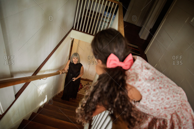 Young girl looking at her grandmother on a stairway