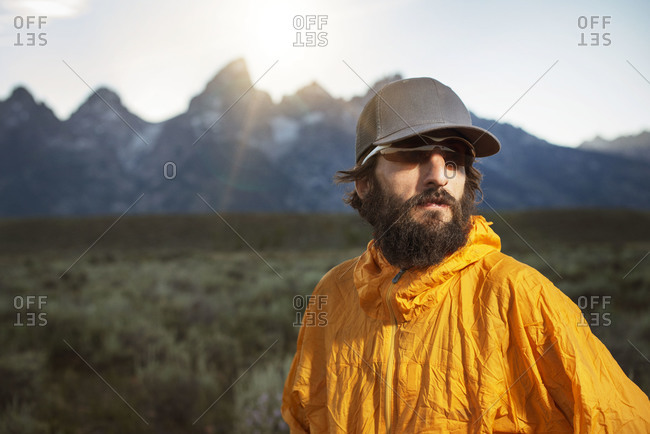 Hiker in a yellow windbreaker in the mountains