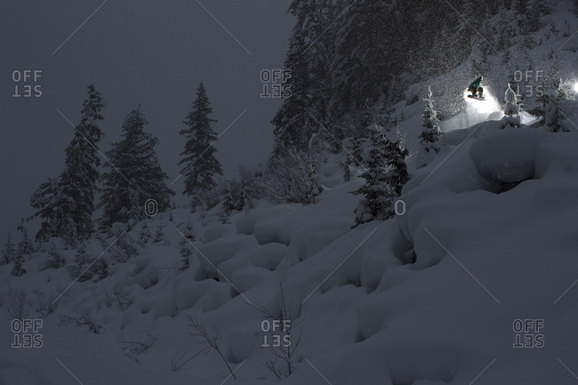 Woman snowboarding at night in British Columbia, Canada