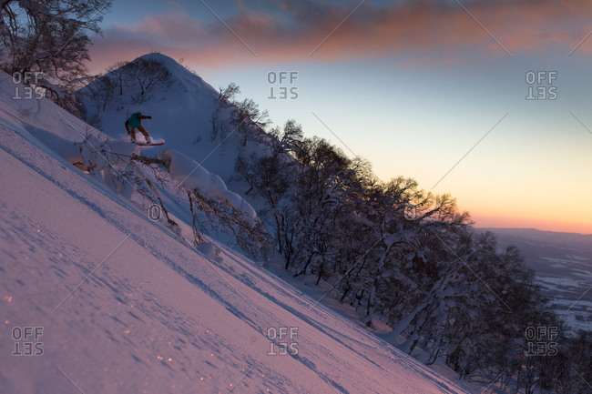 Woman snowboarding at sunset in Japan
