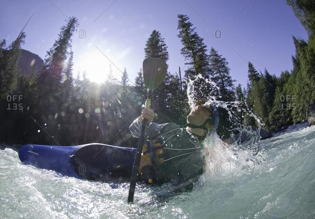 Man losing his balance while kayaking on whitewater