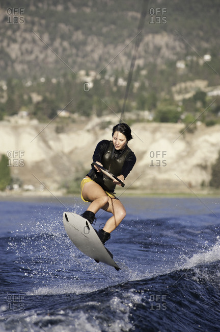 Woman jumping with a wakeboard on a lake in Penticton, Canada