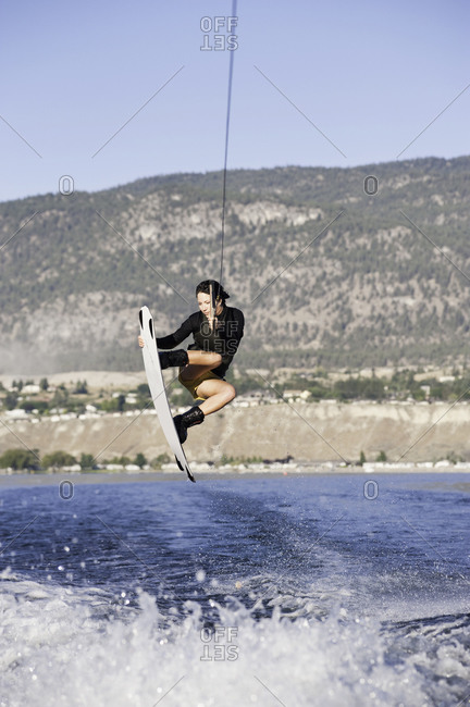 Woman grabbing her wakeboard midair on a lake in Penticton, Canada