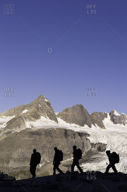 Silhouette of alpinists hiking on a mountain