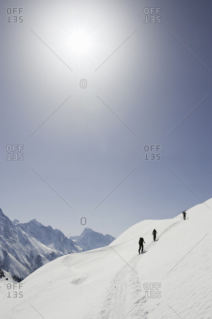 People cross-country skiing uphill