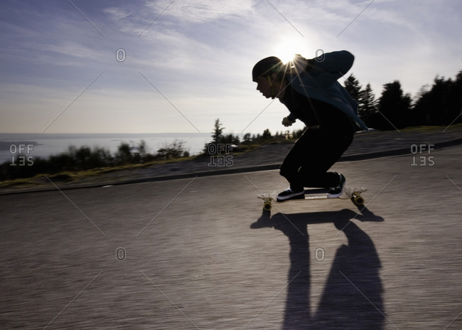 Silhouette of a boy riding skateboard