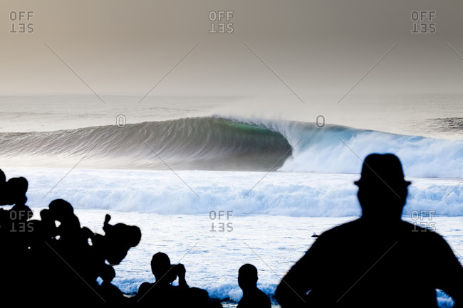 Silhouettes of people staring at an ocean wave