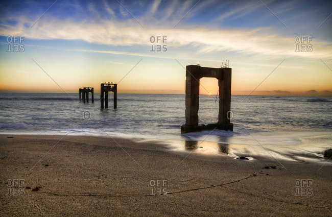 Remains of a pier in the ocean at sunset