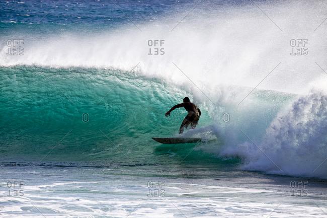 Man surfing in an ocean wave tube