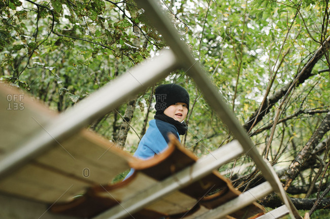 Young boy sitting on a roof in a forest