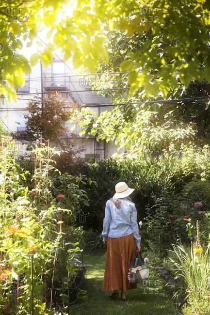 A woman walks through a flower garden