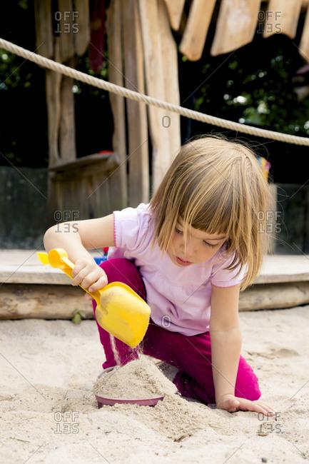 Little girl on playground balancing in sandbox