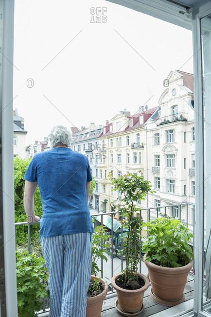 Mature man standing on balcony
