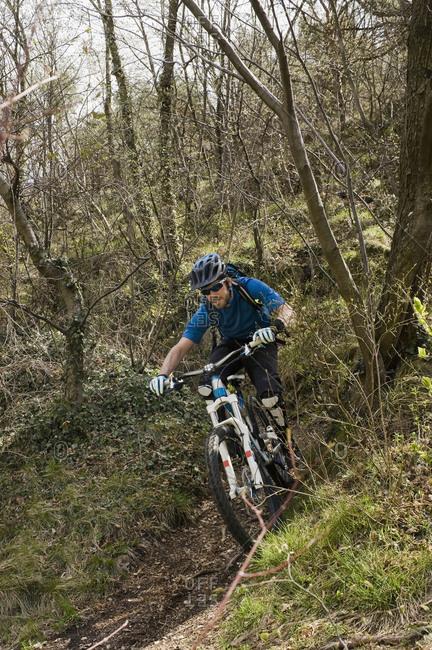 Mid adult man riding mountainbiking, Italy