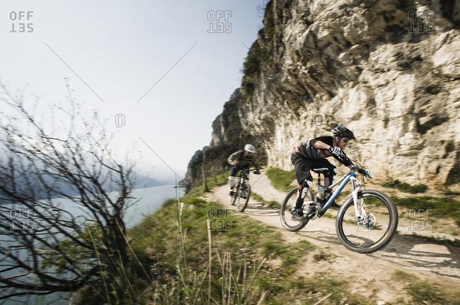 Men riding mountain bike at Lake Garda, Italy