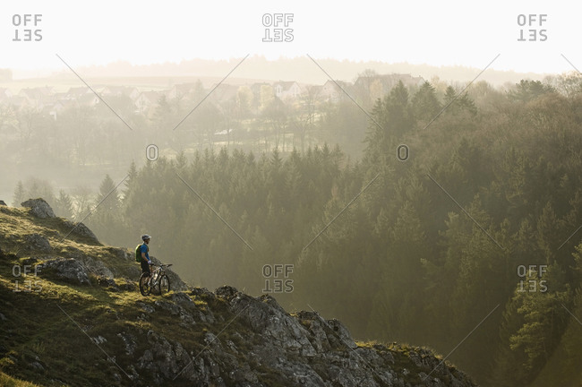 Young man mountainbiking at sunrise, Bavaria, Germany