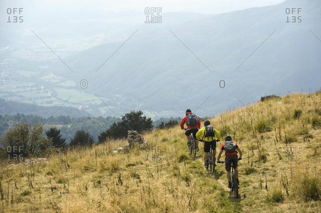 Three mountain bikers on the way downhill, Matajur, Istria, Slovenia