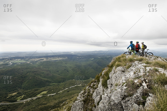 Three mountain bikers looking at view, Vipava valley, Istria, Nanos, Slovenia