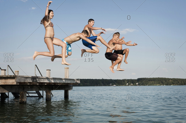 Five teenagers jumping from a jetty into lake