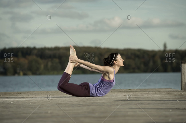 Woman practicing yoga on jetty, Woerthsee, Bavaria, Germany