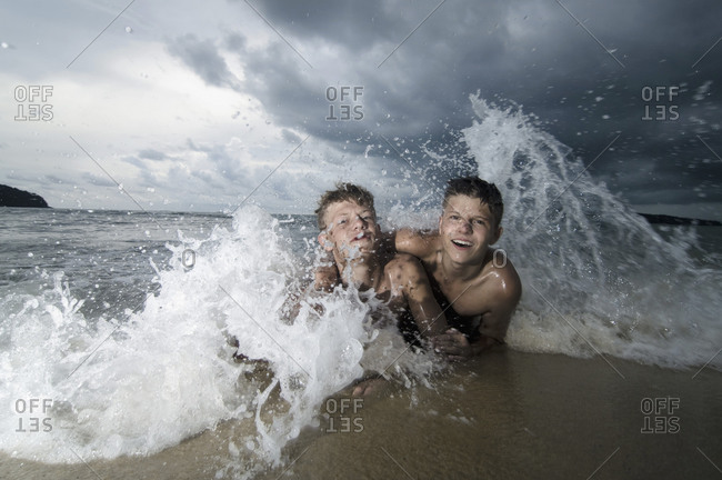 Two boys having fun in ocean, Lankawi, Malaysia