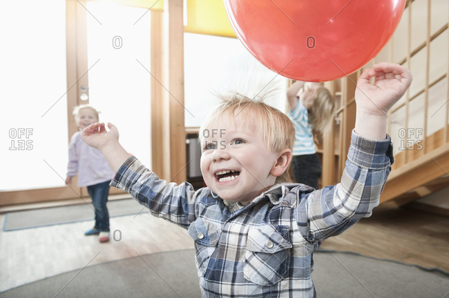Kids playing with red balloons in kindergarten