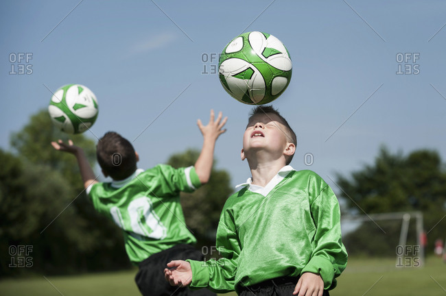 Two young football players learning ball control
