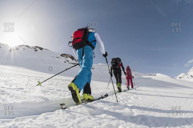 Three skiers climbing steep slope snow winter