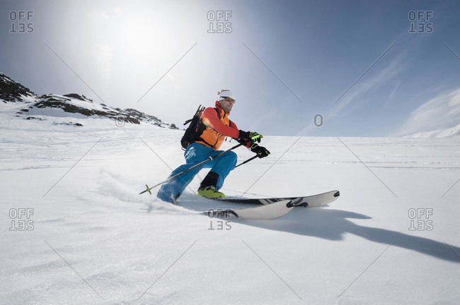 Man skiing downhill powder snow Alps sunshine