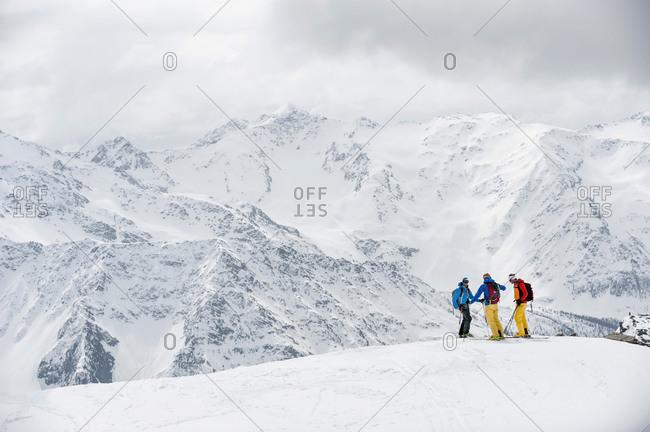 Alps winter mountains three skiers snow