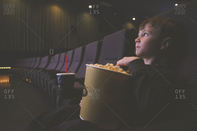 A boy sits in an empty movie theater