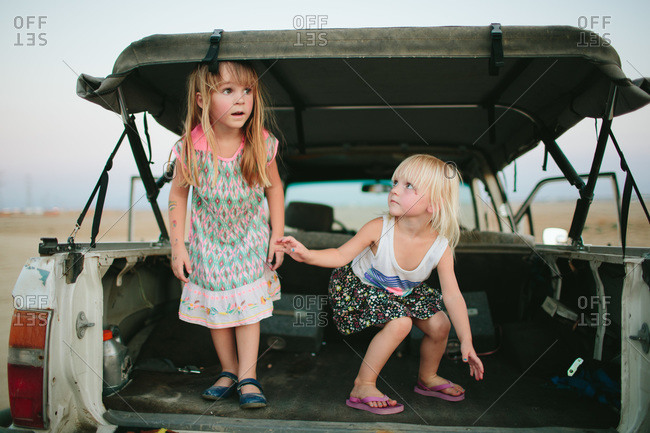 Two girls play in a truck bed