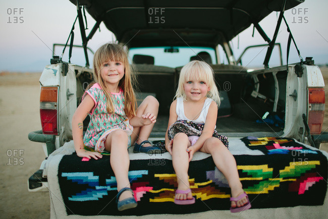 Two girls sit on the bed of a truck