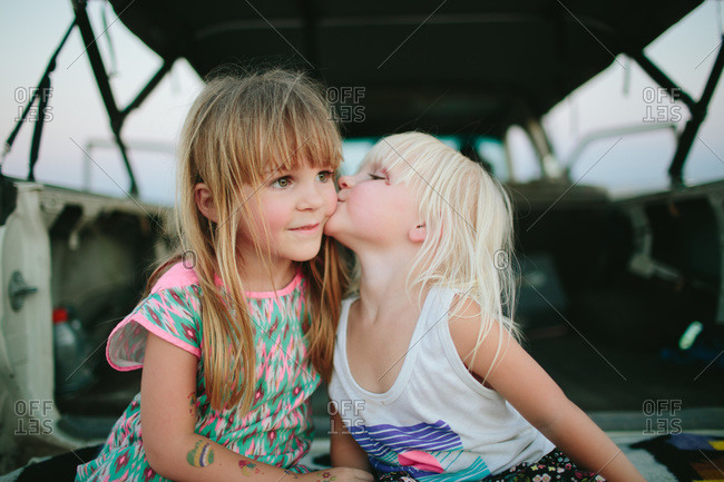 A girl kisses another girl by a truck