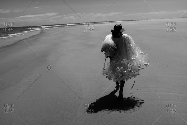 Man carrying fish net at the beach