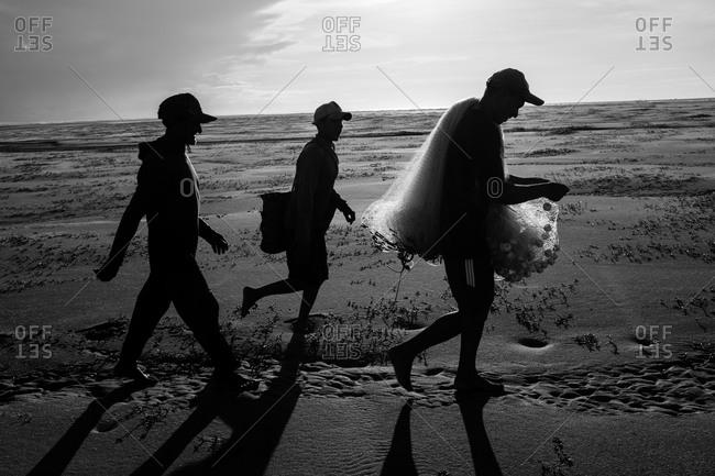 Atins, Maranhao, Brazil - May 6, 2014: Three fishermen going to fish