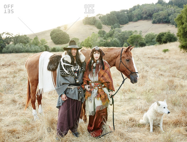 Nomadic couple posing by a horse