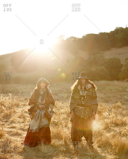 Nomadic couple standing in a field at sunset