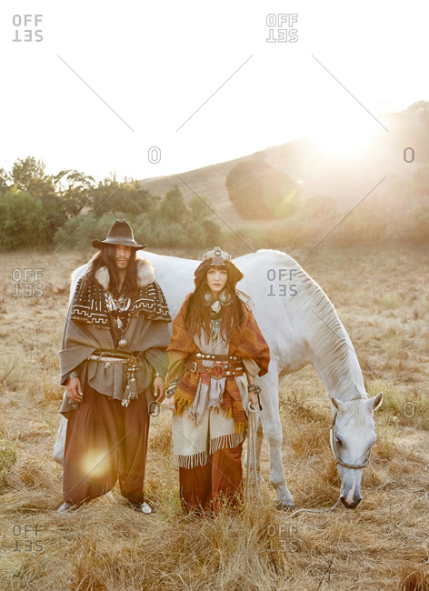 Couple standing in a field by a horse