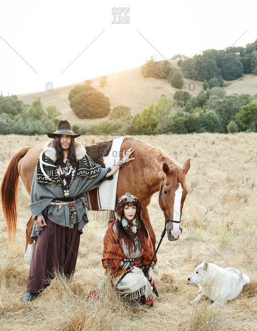 Nomadic couple posing with a horse and wolf
