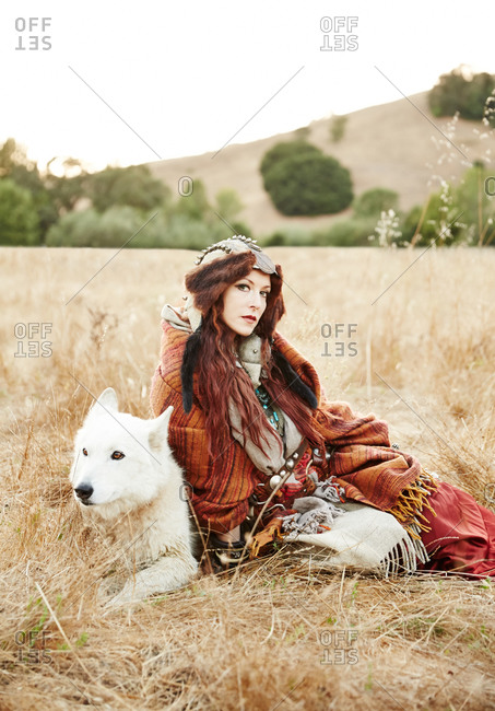 Woman posing by a wolf