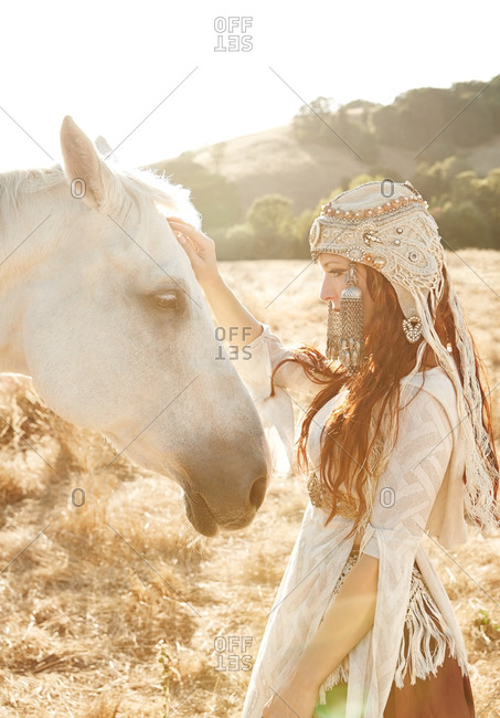 Woman petting a horse at sunset