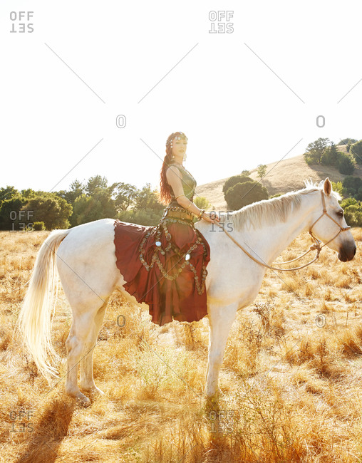 Side view of woman riding a horse