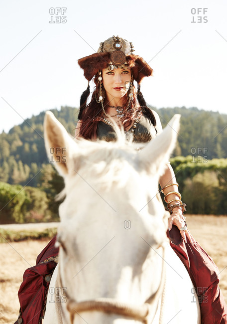 Woman riding a horse in nomadic clothing