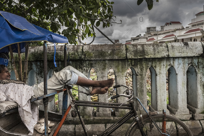 India - July 31, 2014: Cycle rickshaw driver takes a rest